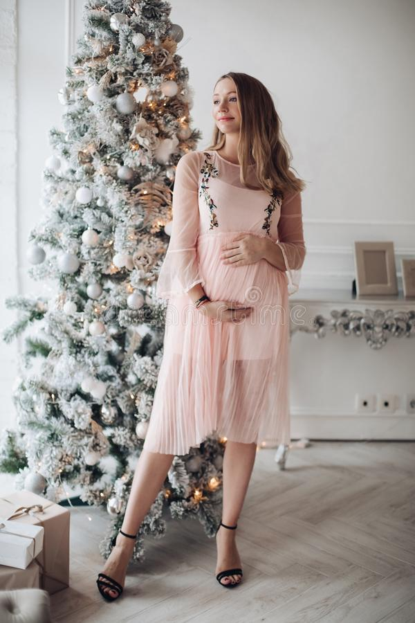 Close-up tenderness female hand hugging pregnant tummy feeling fondness at Christmas tree. Background. Caring future mother enjoying pregnancy wearing pink royalty free stock images