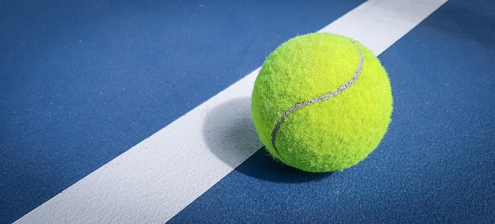 A close-up of the tennis ball on the court. The blue background is a beautiful illustration and background. Close-up shots of tenn royalty free stock photography