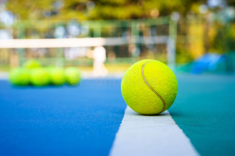 Tennis ball on white Court line on hard modern blue court with Net balls player trees in the background royalty free stock photography