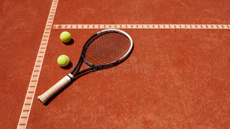 Close up of tennis balls and racket on dross. At tennis court stock image