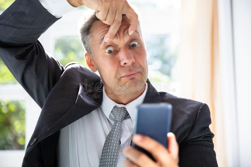 Terrified Businessman Looking At Mobile Phone Screen royalty free stock photos