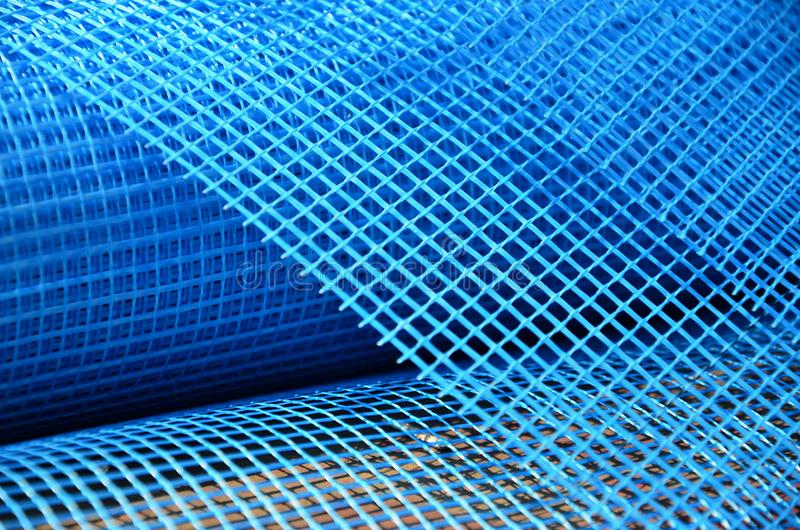 Close-up texture of a blue reinforcing mesh rolled up in a roll. Building resource for reinforcing walls in the process of their royalty free stock photo