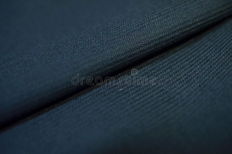 Close up texture dark blue fabric with stripe line of suit. Photo shoot by depth of field for object stock photography