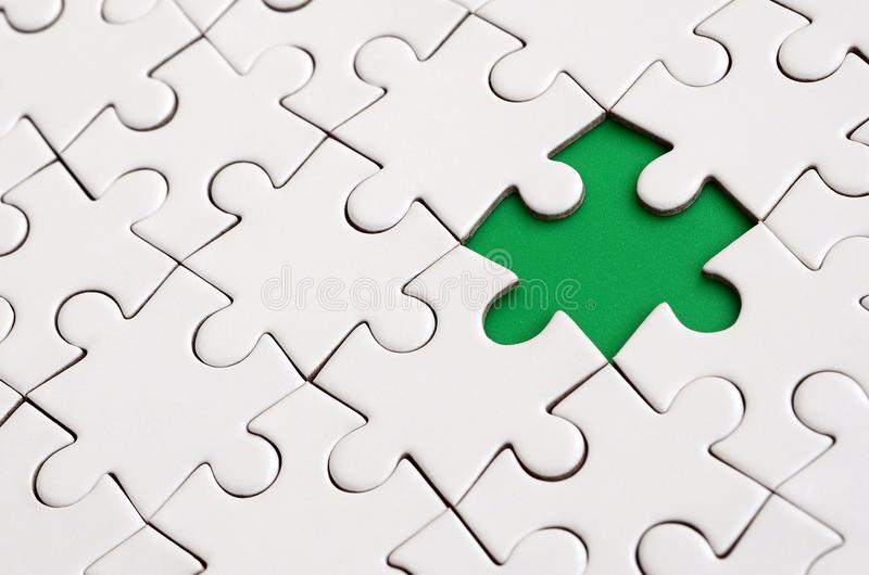 Close-up texture of a white jigsaw puzzle in assembled state with missing elements forming a green pad for text. Copy space. Close-up texture of a white jigsaw stock photography