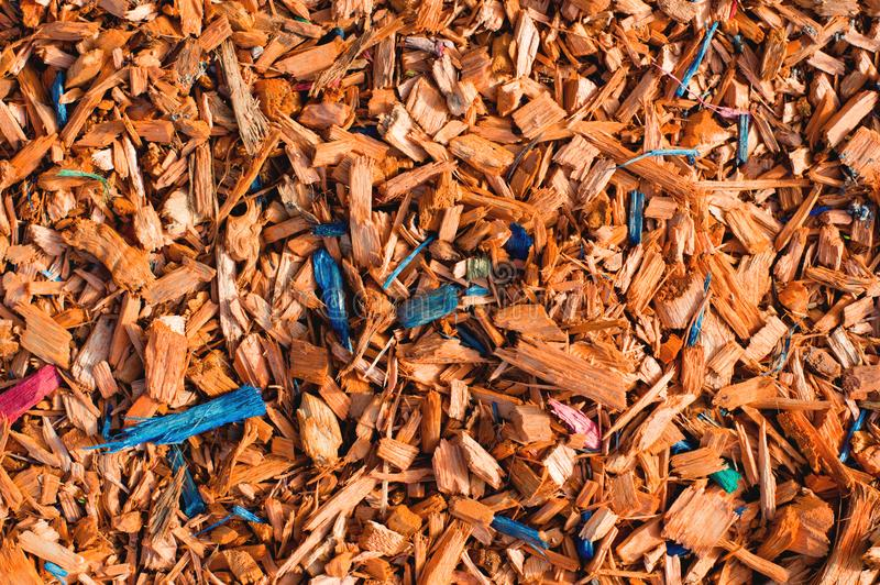 Close-up Textured background decorative colored sawdust for finishing flowerbeds in the winter season. Yellow orange stock image