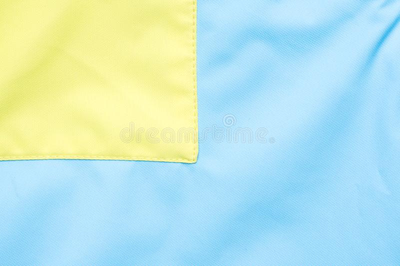 Close-up of textured fabric cloth textile background, Yellow and blue part of jacket royalty free stock images