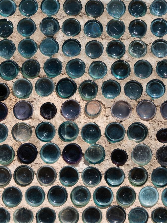 Close up textures of wall made with glass bottles in vertical format. Close up textures of wall made with glass bottles embedded in concrete mortar in vertical royalty free stock image