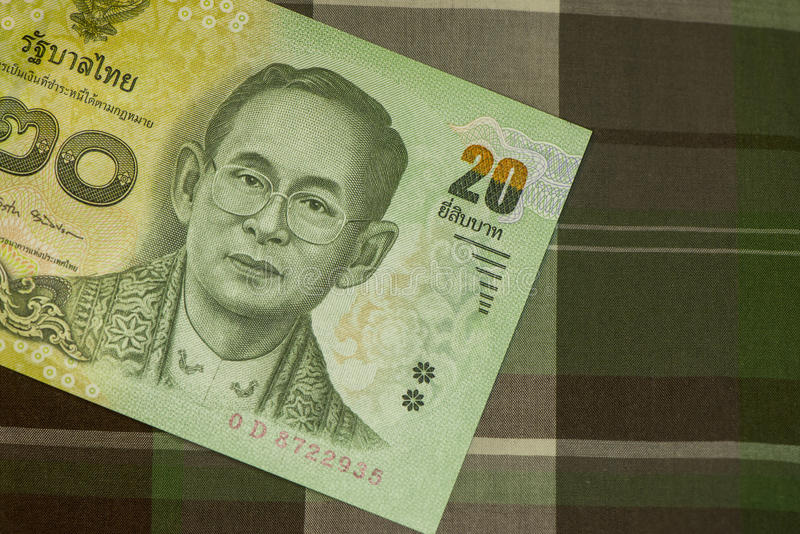 Close up of Thai banknote Thai bath with the image of Thai King. Thai banknote of 20 Thai baht on Green Scottish fabric. stock photos