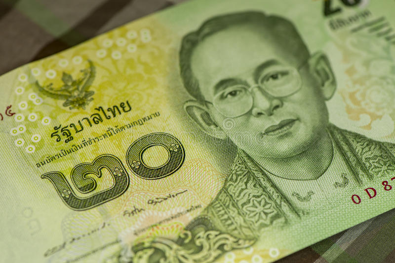 Close up of Thai banknote Thai bath with the image of Thai King. Thai banknote of 20 Thai baht on Green Scottish fabric. stock images
