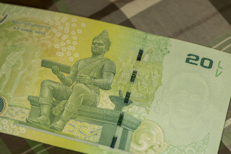 Close up of Thai banknote Thai bath with the image of Thai King. Thai banknote of 20 Thai baht on Green Scottish fabric. royalty free stock photos