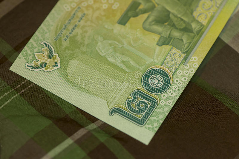 Close up of Thai banknote Thai bath with the image of Thai King. Thai banknote of 20 Thai baht on Green Scottish fabric. royalty free stock images