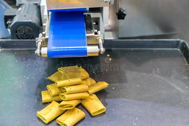 Close up thai dessert name tong muan or tong pup Roll or fold wafer on tray of automatic sweets making machine in production. Line for high technology of stock image