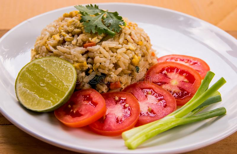 Close up Thai food, fried rice with eggs and pork served with fresh tomato slice, spring onions and lemon slice on white plate. Fried rice with eggs and pork stock photography