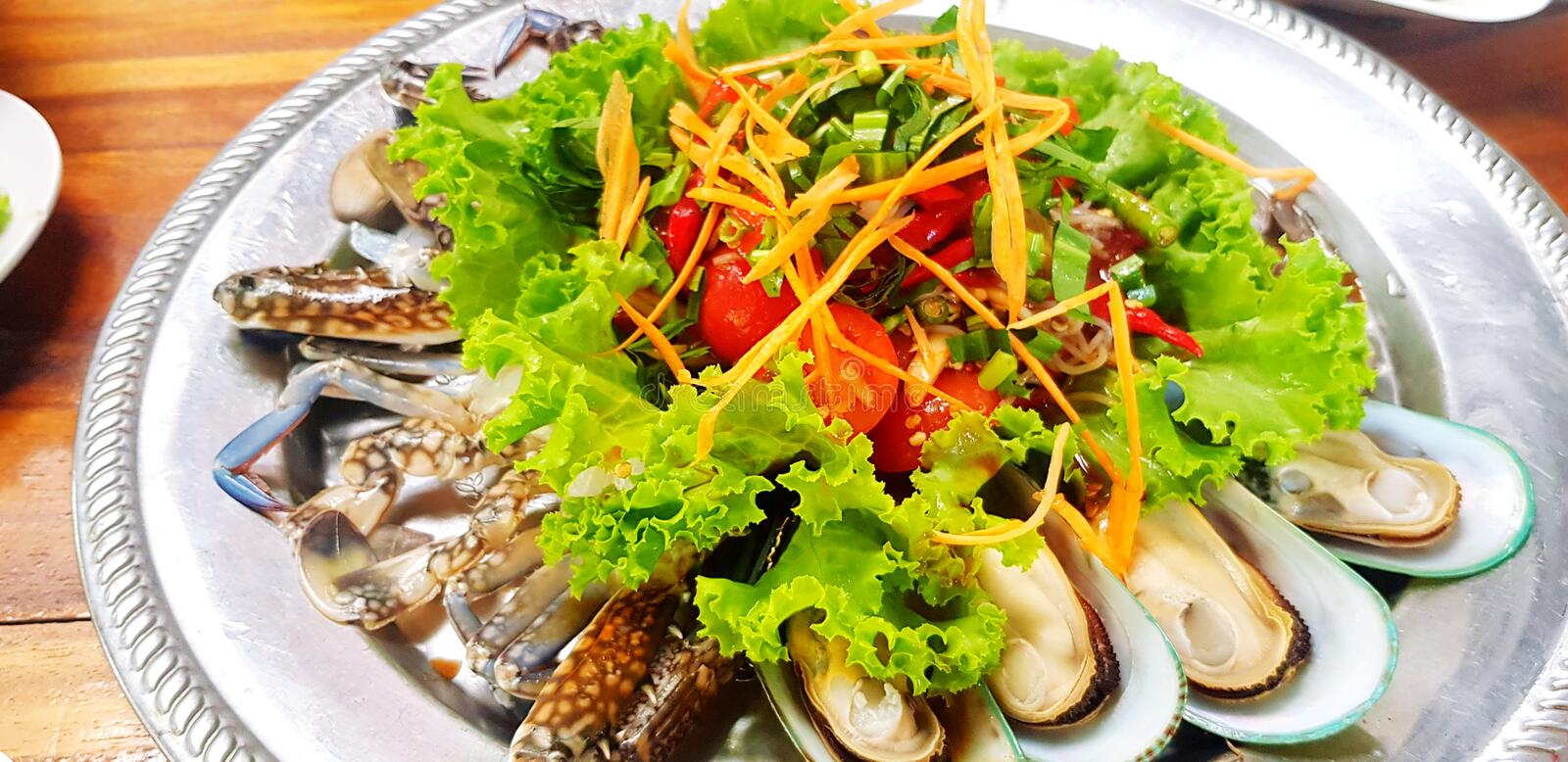 Close up Thai papaya style and vegetable salad with seafood, fresh mussel, prawn and blue crab stock photos