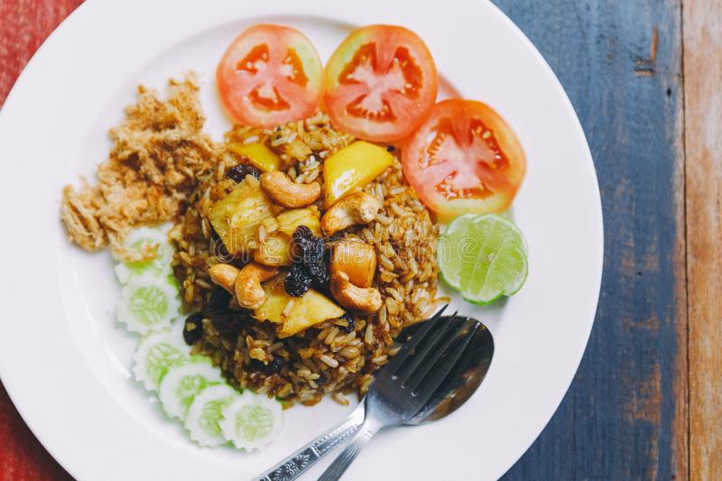 Close up Thai Pineapple Fried Rice topping with raisin, cashews and dried shredded pork. Served with cucumber and tomato.  stock images
