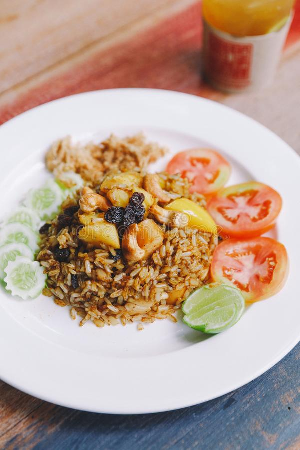 Close up Thai Pineapple Fried Rice topping with raisin, cashews and dried shredded pork. Served with cucumber and tomato.  royalty free stock photography