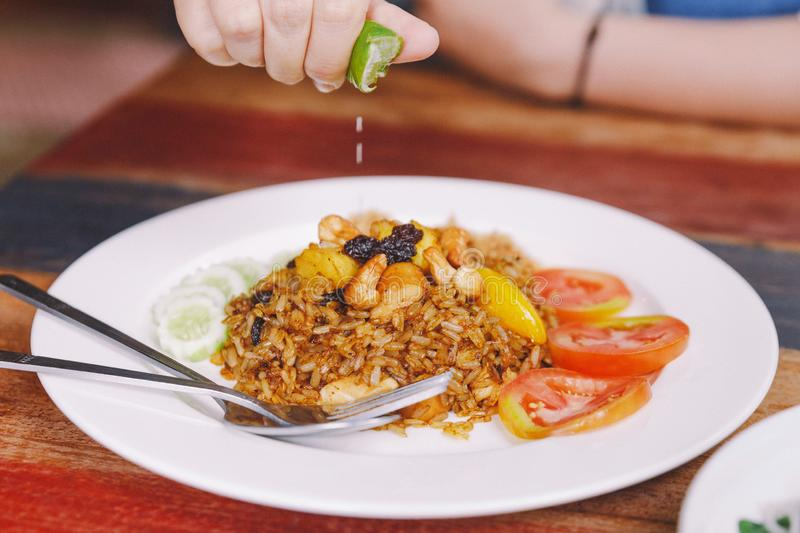 Close up Thai Pineapple Fried Rice topping with raisin, cashews and dried shredded pork. Served with cucumber and tomato. Close up Thai Pineapple Fried Rice stock image