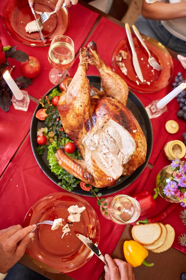 Family eating traditional Thanksgiving turkey on a festive table background. Roasted turkey. Family celebration concept. royalty free stock image