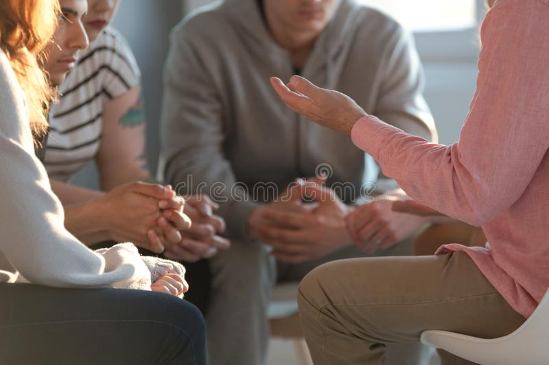 Close-up of a therapist gesticulating while talking to a group o. F listing teenagers during an educational self-acceptance and motivation meeting stock photo
