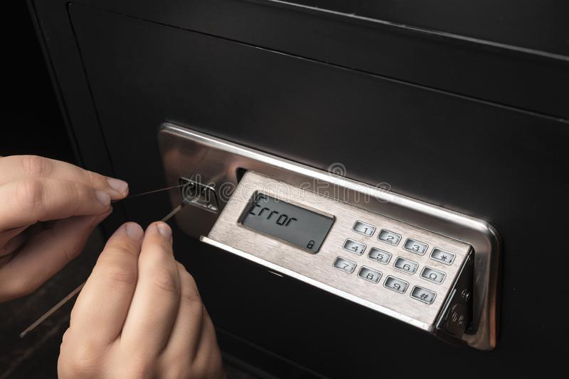 Close-up of Thief`s hands attempting to Break Home Money Safe and perform Robbery stock photography