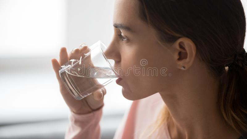 Close up of thirsty girl enjoying pure mineral water stock photography