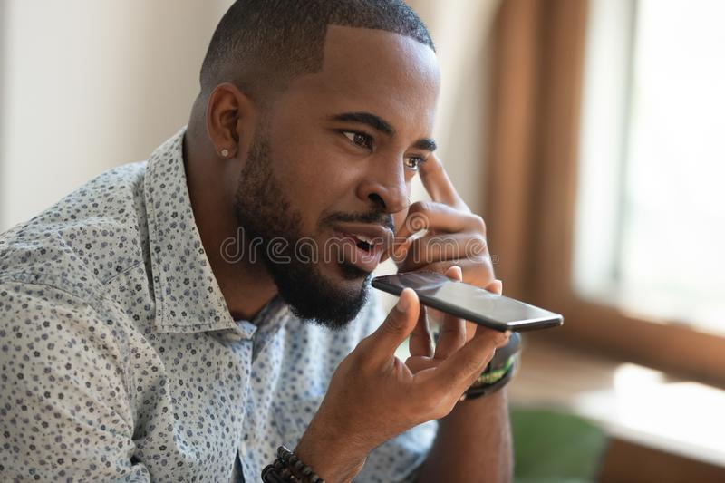 Close up thoughtful african american guy using virtual assistant. Close up thoughtful mindful african american guy sitting on couch, talking on speakerphone royalty free stock photos