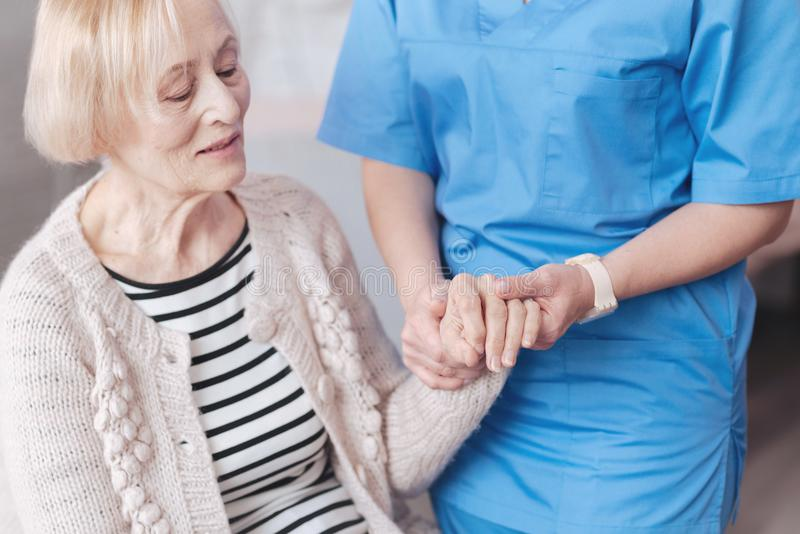Close up of thoughtful nurse holding hand of elderly patient. Helping is what matters. Emotionally exhausted senior lady sitting on the edge of her sofa and royalty free stock photography