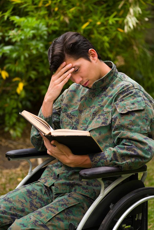 Close up of a thoughtful young soldier sitting on wheel chair reading a book in the patio, in a backyard background.  stock photo