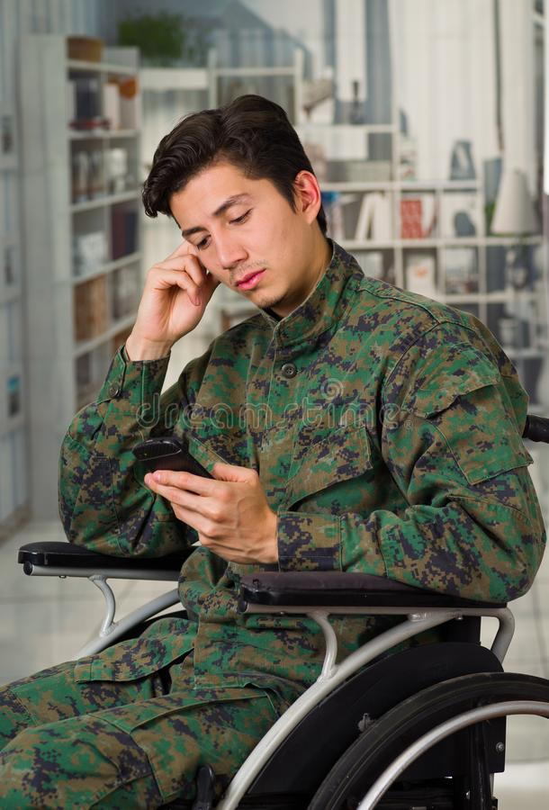 Close up of a thoughtful young soldier sitting on wheel chair using his cellphone, in a blurred background.  royalty free stock image