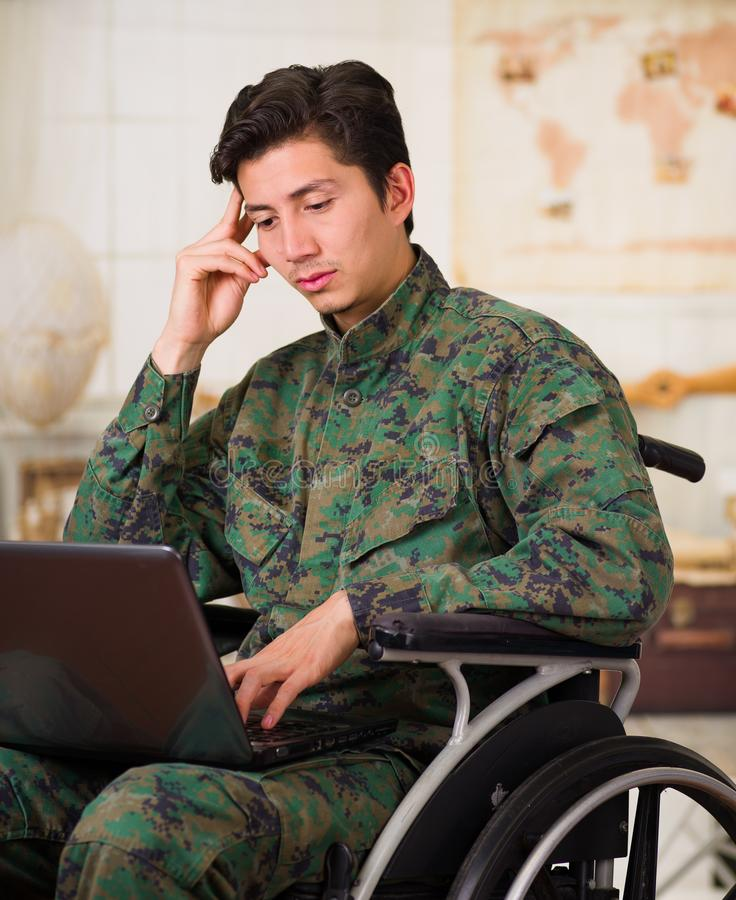 Close up of a thoughtful young soldier sitting on wheel chair using his computer over his legs, wearing military uniform royalty free stock photo