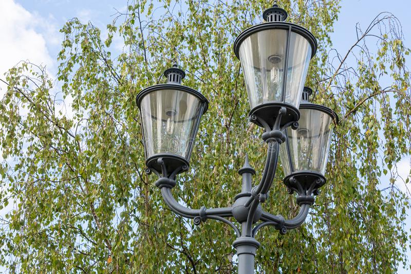 Close-up of three black street lamps on one column against green tree and sky. Close-up of three black street lamps on one column against blue sky anf green tree stock photography