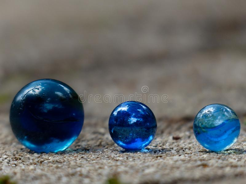 Close up of three blue glass marbles in a row with blurred background space to place text stock photography