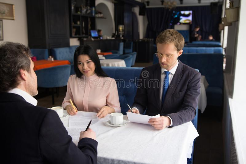 Three business people sign agreement at restaurant stock images