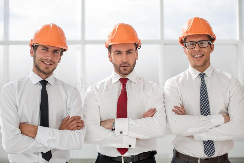 Close up.three confident business men in protective helmets royalty free stock photo