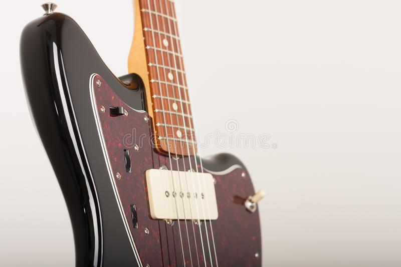 Close up of three controls on black electric guitar, studio shoot. Red tortoise shell pickguard, alder body, two single coil.  stock images
