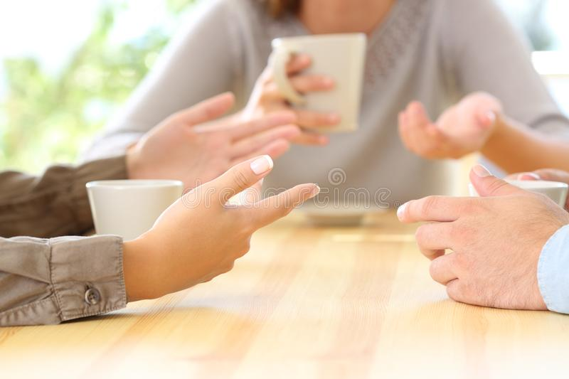 Three friends hands talking in a bar. Close up of three friends hands talking sitting in a bar or house royalty free stock image
