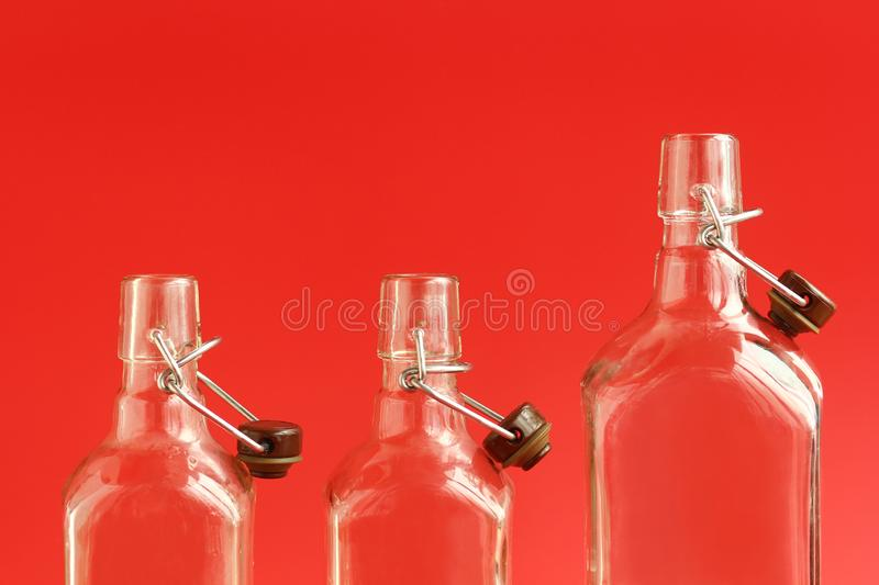 Close up of three glass empty open alcohol bottles over red background. Closeup of three glass empty open alcohol bottles over red background royalty free stock photos