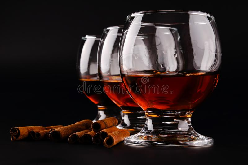 Close up of three goblet glasses in a row with cognac, dark rum or brandy and scattered cinnamon sticks on a black background with royalty free stock photos