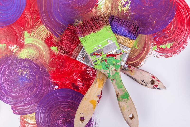 Close up three paint brushed stacked fanned out on swirl textured background purple red green royalty free stock photos