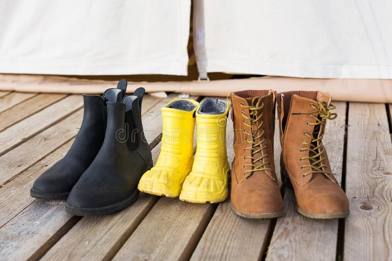 Close-up of three pair of shoes on wooden terrace behind of glamping tent. Family camping concept stock image