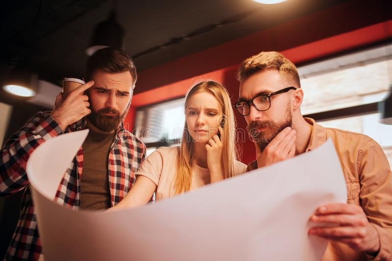 Close up of three people looking to the big piece of paper and studying the information from it. They are making some stock images