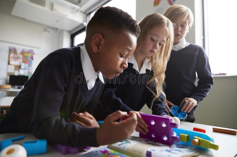 Close up of three primary school children working together with toy construction blocks in a classroom, low angle, side view royalty free stock images