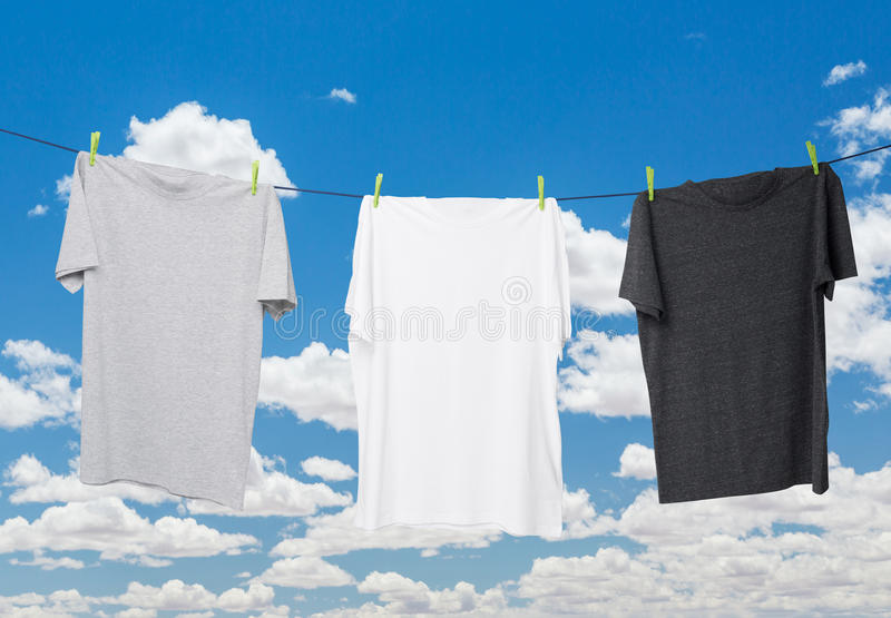 Close up of three t-shirts on the rope (grey, white and dark grey). Cloudy sky background stock images
