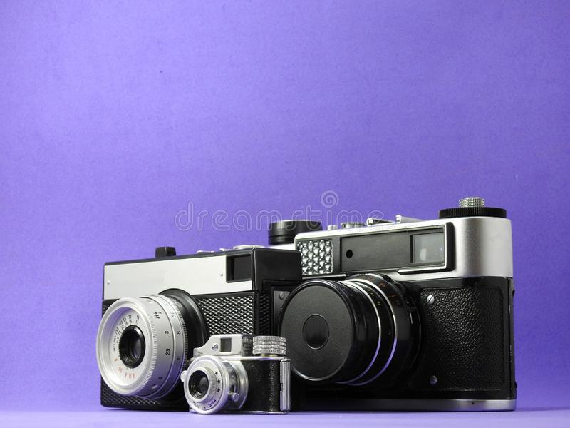 Close-up of three vintage analog photographic cameras. One of them is a miniature. Lilac background royalty free stock images