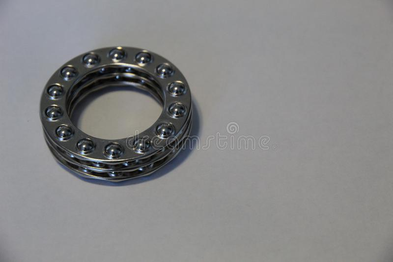 Close up of Three Wheel Ball Bearings Stacked up. Close up of three shiny wheel ball bearings stacked up balls down on white background stock image