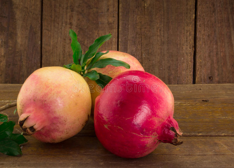 Close up of three whole pomegranates on wood background stock photo