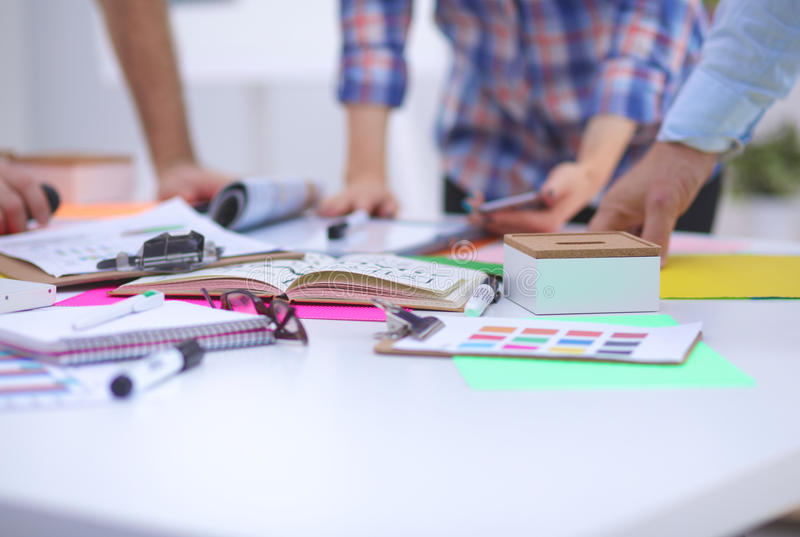 Close-up of three young creative designers working on project together. Team work stock image
