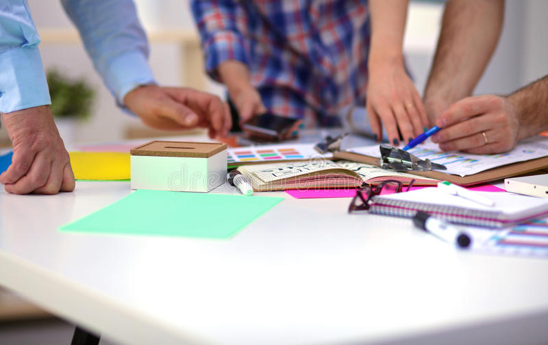 Close-up of three young creative designers working on project together. Team work stock photography