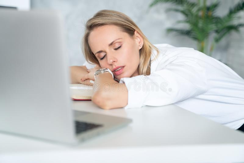 Close up of a tired businesswoman wearing white clothes and sleeping near her laptop in an office with white and green binders stock photo
