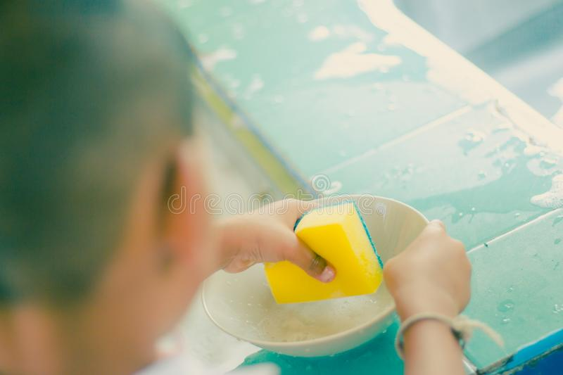 Close up to hands of Kindergarten student is cleaning dish. stock photo
